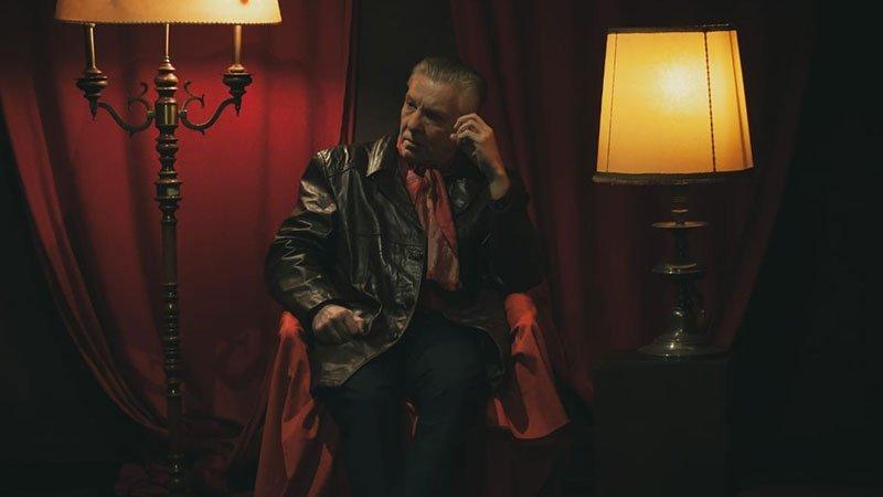 Foto promocional de Mark Snarski en la que se le ve sentado en un sillón mirando al infinito en la penunmbra de una habitación con cortina roja de fondo y una lámpara a cada lado.