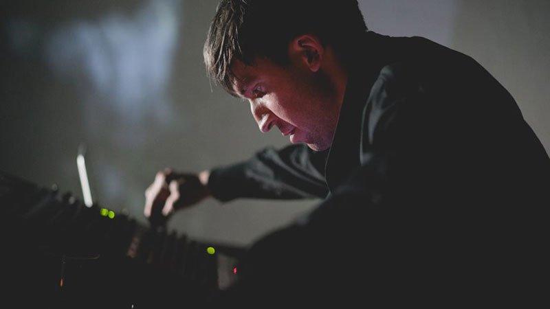 Foto de Samuel Kerridge retorciendo los controles de la mesa de mezclas en directo