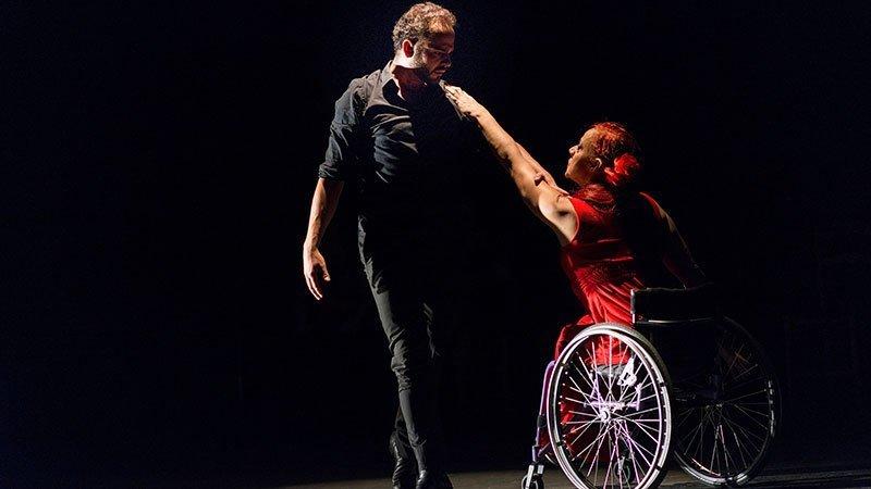 Escena de la coreografía de Sueños reales de cuerpos posibles, donde se ve a José Galán de pie bailando con Lola López en su silla de ruedas
