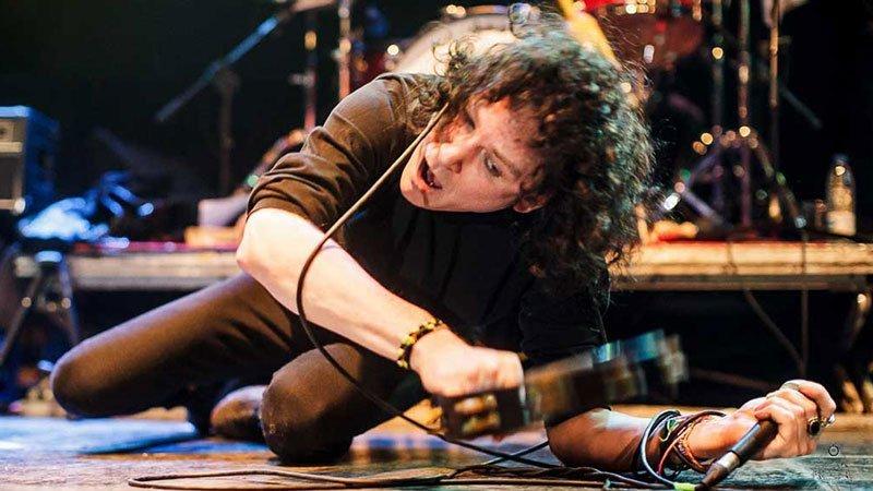 El cantante de The Cynics, Michael Kastelic por los suelos en uno de sus conciertos en 2015 (foto por Dena Flows)