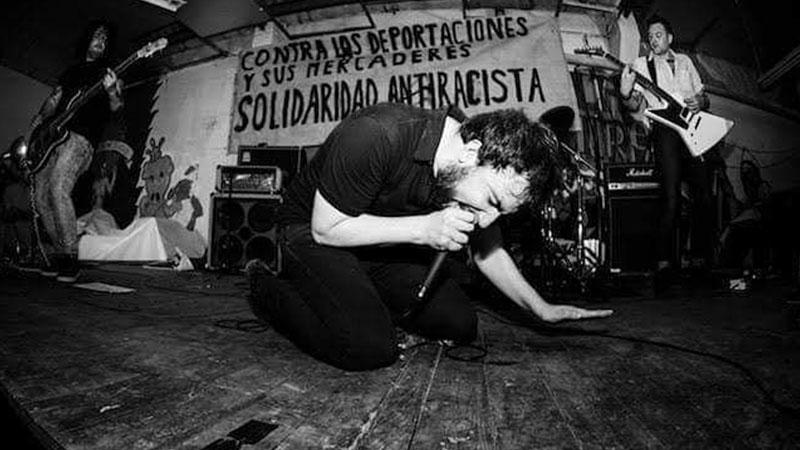 Foto de Una Bèstia Incontrolable tocando en directo, donde se ve al cantante arrollidado en el suelo, gritando a ojos cerrados demostrando una gran energía