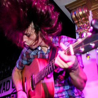 El cantante y guitarrista de Wi Bouz dándolo todo en directo con su pelo suspendido en el aire