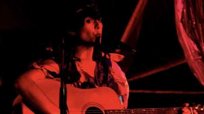 Foto de Yanira en directo cantando y tocando su guitarra