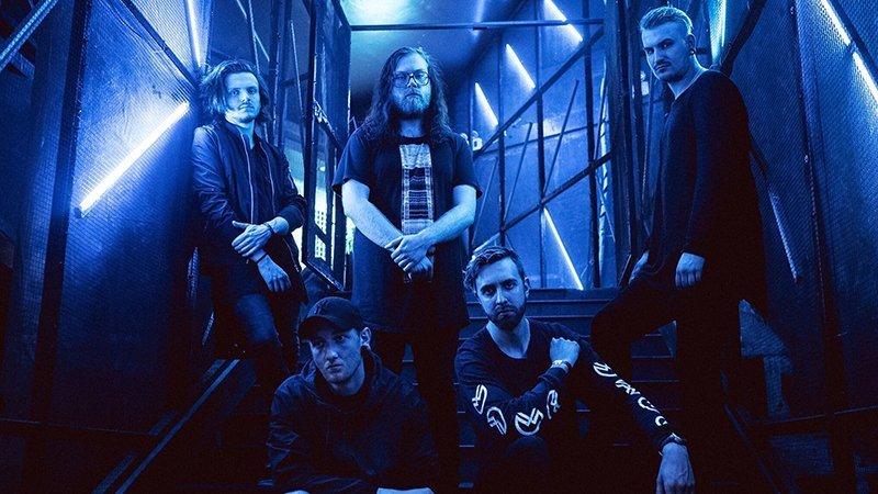 Foto promocional de los cinco miembros de Awake the Dreamer posando muy serios en unas escaleras con luces azules