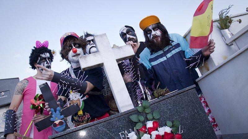 Foto de los miembros de The Black Panthys Party posando en un cementerio ataviados con estética tipo Kiss, cruz invertida con Pocoyo crucificado, bandera española con cruz de David pintada, lazo rosas, nariz de payaso, bastoncillos haciendo de pinchos en las muñequeras, vestido rosa chicle, camiseta de Krusty el payaso... un cuadro, vaya