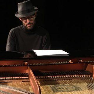 Foto de Borja R. Niso tocando el piano con sombrero de ganster y cara de enamorado de la música