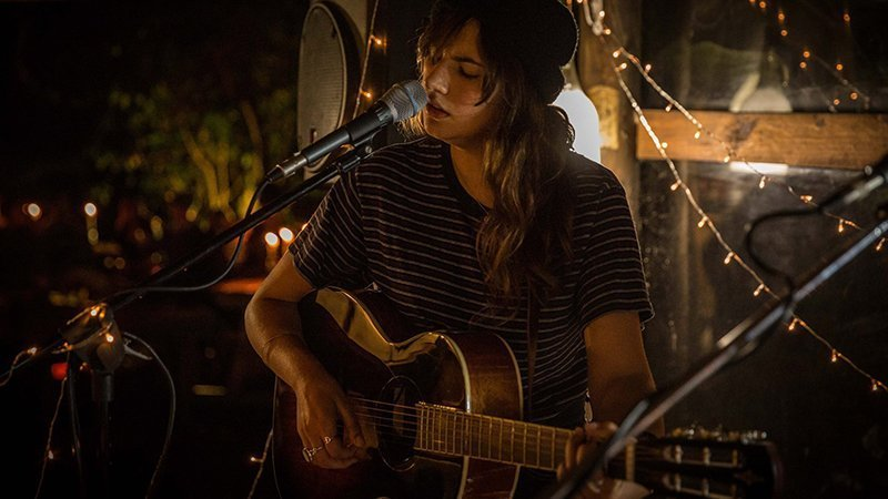 Foto de Chantel Van T tocando en directo con su guitarra en una habitación con luz tenue y gesto de sentimiento profundo en su cara