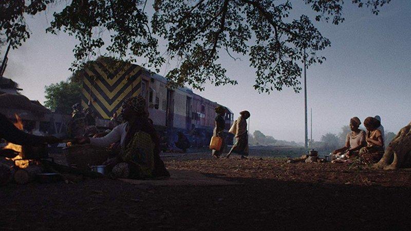 Fotograma de la película en el que se ve un plano general desde el suelo, donde puede apreciarse el tren en el fondo, en el centro dos mujeres caminan de izquierda a derecha y a los lados varias mujeres sentadas en el suelo junto al fuego