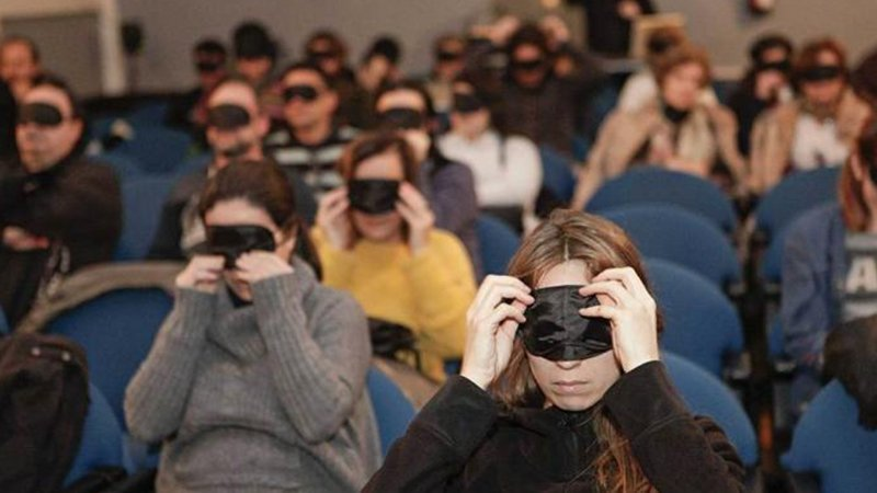Foto de un patio de butacas lleno de gente con los ojos tapados con antifaces negros