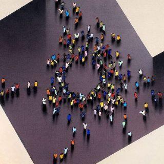 Detalle del cuadro Cuatro caminos, de Juan Genovés, en el que puede verse una vista cenital lejana de un corro de gente en medio de una construcción geométrica que describe cuatro caminos que llegan a una plaza cuadrada