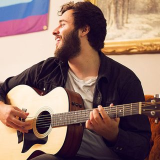 Foto de Guilhem tocando su guitarra sentado en un sofá, con cara de bueno mirando a la izquierda y sonriendo