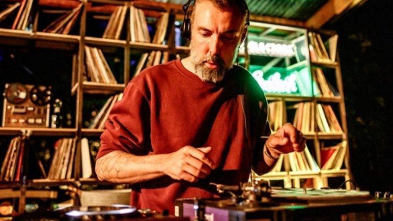 Foto de Intergalactic Gary delante de los platos, con los ariculares puestos en un solo oído y cara de concentración en una de sus sesiones DJ