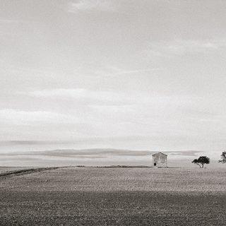 Detalle de una fotografía del artista murciano Jose Quintanilla donde se puede ver una enorme llanura con una pequeña casa y un árbol a lo lejos