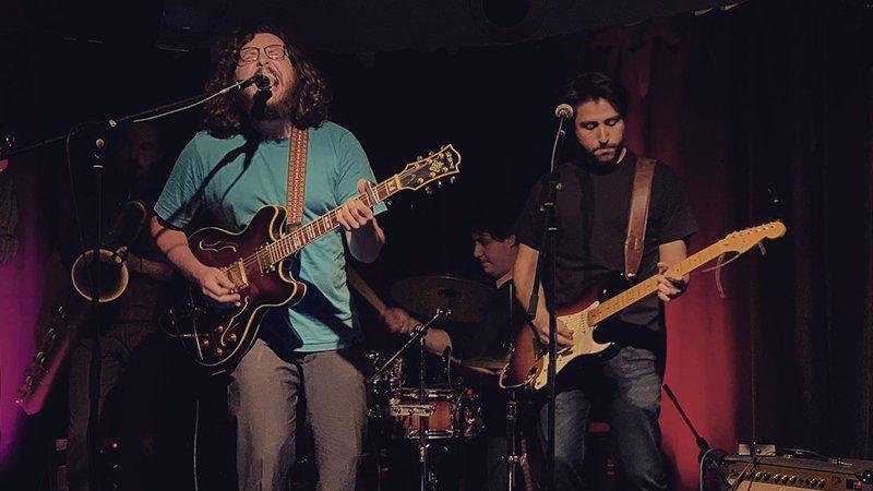 Foto de Mingote tocando en directo, se puede ver a Germán, el frontman, guitarra en mano cantando con gesto de amplio sentir en la cara