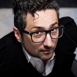 Foto de primer plano del escritor Patricio Pron mirando a cámara con gesto de complicidad