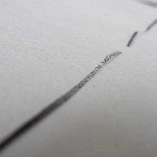 Foto de la producción de la exposición en la que se ve una linea irregularmente discontinua sobre un papel