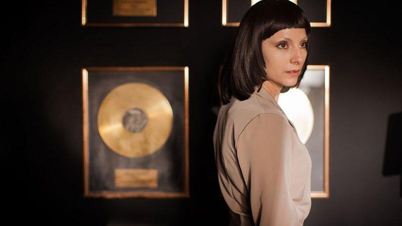 """Fotograma de la película """"Quien te cantará"""" donde se ve a la protagonista, Najwa Nimri, de costado ante una pared con varios discos dorados enmarcados, a modo de trofeos de la música"""