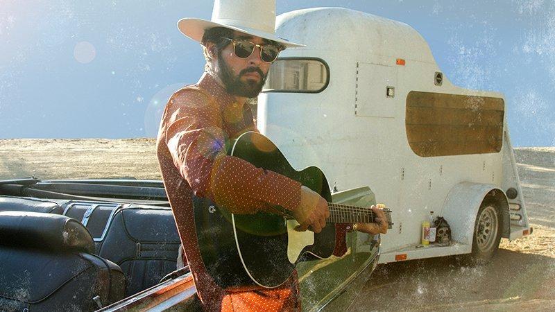 Foto promocional de Ryan Bingham donde se le ve con su guitarra en manno ante una caravana y un cochde muuuy típicos americanos