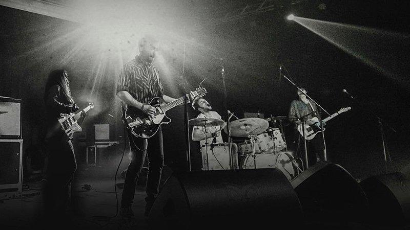 Foto en blanco y negro de la banda tocando en directo donde se ve a los cuatro miembros cada uno en su puesto, de izquierda a derecha: bajo, guitarra y voz, batería y voz, y segunda guitarra
