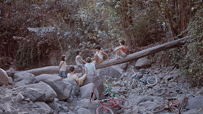 Fotograma de la película en la que se ve a un grupo de niños hablando entre si en un entorno de rocas y subidos a un tronco de árbol caído, con sus bicis apoyadas debajo