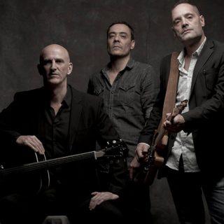 Foto promocional de los tres miembros base de la banda The 44 Dealers, posando en un estudio fotográfico con tela oscura de fondo, luz tenue, sus guitarras en la mano y gesto serio interesante