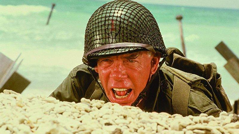 Fotograma de la película en el que se ve a Lee Marvin en un primer plano, ataviado con traje de guerra, casco con redecilla y cara de acción, con gesto de estar gritando a su cuadrilla