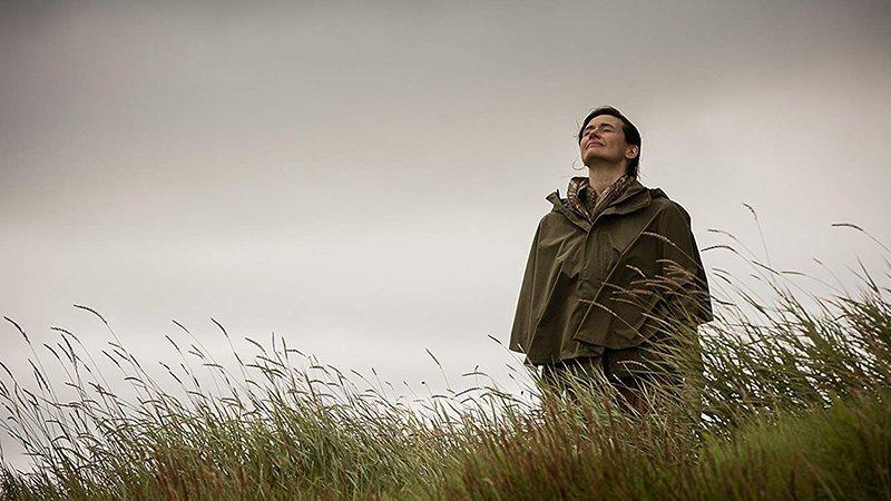 Fotograma de la película en el que se ve a la protagonista Emily Mortimer de pie en una pradera con los ojos cerrados y la cabeza alta, oliendo y sintiendo el entorno