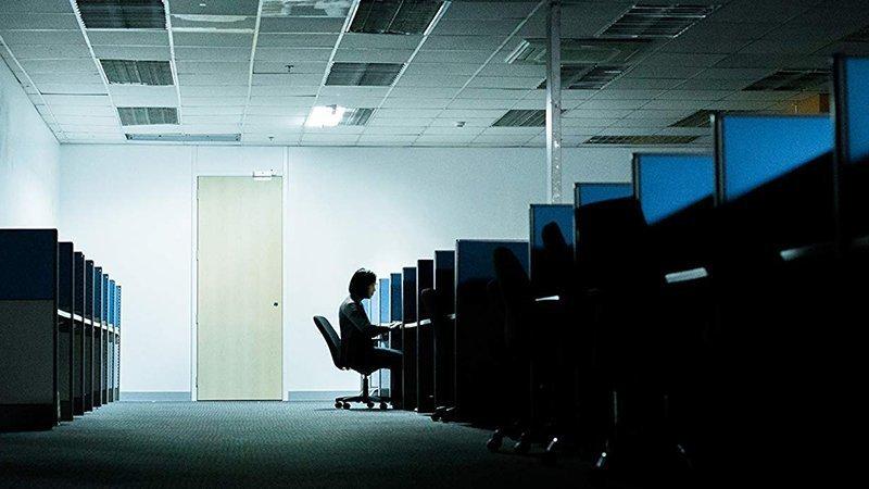 Fotograma del documental The Cleaners en el que se ve una oficina llena de puestos de trabajo vacíos en perspectiva caballera. Es por la noche y solo en uno de los puestos hay una chica sentada ante el ordenador