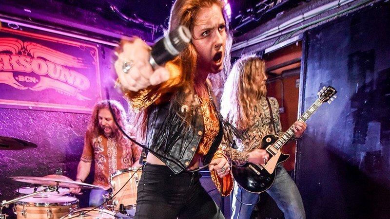Foto de 3 de los miembros de The Mothercrow en pleno directo, en primer plano la cantane con cara de velocidad estirando el brazo cual lanzando un puñetazo agarrando un micrófono de los 70