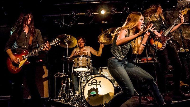 Foto de la banda tocando en directo donde puede verse a los 5 miembros en acción