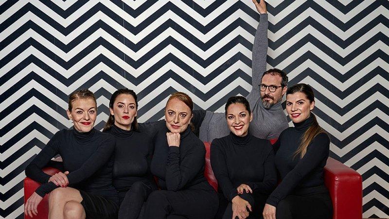 """Foto del elenco completo de la obra """"Todas las mujeres"""" posando en un sofá rojo sobre una pared con lineas blancas y negras"""
