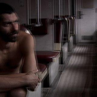 Fotograma de la película Treblinka en la que se ve la perspectiva del pasillo de un vagón de tren con asientos a cada lado y un hombre desnudo sentado en el asiento de la izquierda mira al infinito con gesto pensativo