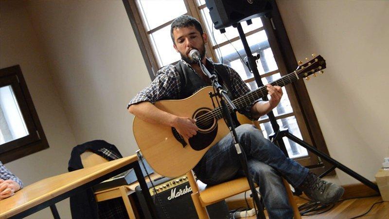 Foto de Ún de Grao tocando en directo en la que se ve sentado con su guitarra y dirigiéndose al micrófono