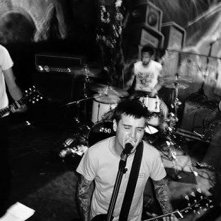 Foto en blanco y negro de Weak tocando en directo, donde se ve delante a los dos baterías y cantantes y de fondo al bajista a la derecha y el batera a la izquierda
