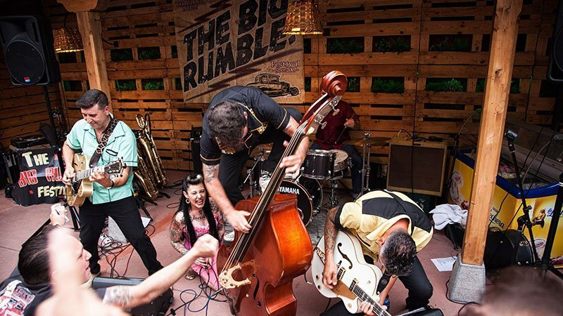 Foto de un concierto en el Big Rumble 2018 en la que se ve a tres músicos en plena acción tocando enérgicamente el contrabajo y la guitarra ante un público muy volcado