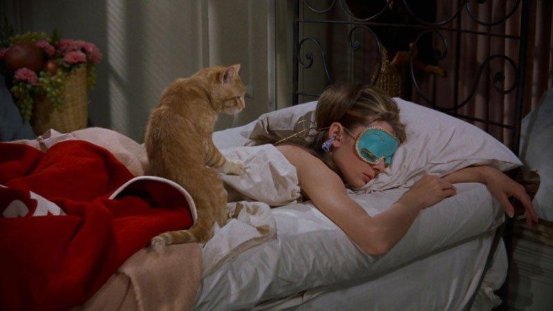 Fotograma de Breakfast at Tiffany's en el que se ve a Audrey Hepburn tumbada en la cama boca abajo con el antifaz color turquesa puesto mientras su gato se sube a su espalda intentando despertarla