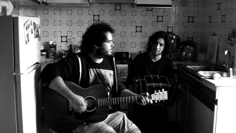 Foto en blanco y negro de César Maltrago tocando la guitarra y Nico Córdoba tocando el bandoneón sentados en una cocina