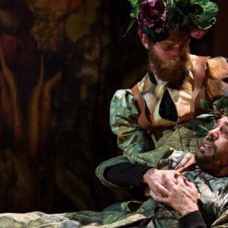 Foto de una escena de la obra en la que se ve a uno de los personajes, con sombrero de frutas y flores sosteniendo en brazos a otro que mira al infinito con gesto dramático