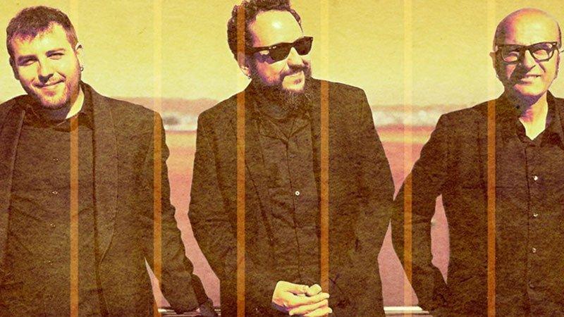 Foto promocional de los tres integrantes del trío vestidos con traje negro apoyados en una barandilla y posando desinteresadamente con el mar de fondo