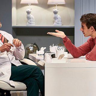Foto de un momento de la obra en el que se ve a sus dos protagonistas sentados ante una mesa hablando