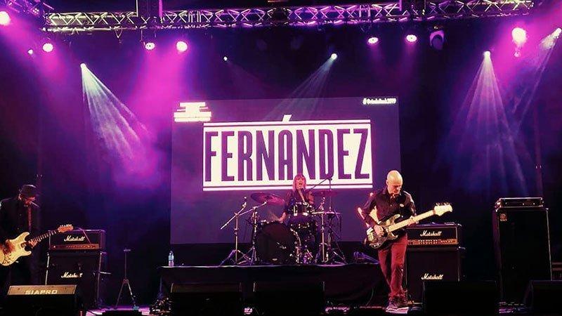 Foto de los integrantes de Fernández tocando en directo en un escenario con el logotipo de la banda detrás. Se ve a Sofía Fernández en el centro, sentada ante su batería mientras canta con energía, más adelante puede verse al bajista a la derecha y al guitarrista a la izquierda.