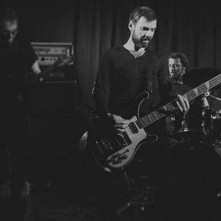 Foto de Humo tocando en directo donde se ve a tres de sus miembros ante sus instrumentos concentrados y dándolo todo en un aura de paz y armonía energética