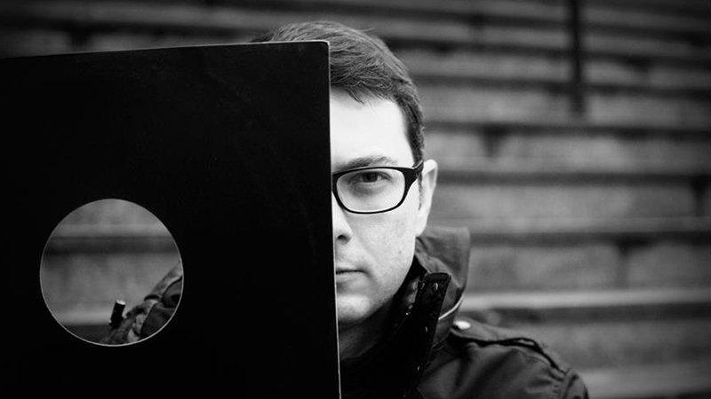 Foto en blanco y negro en la que se ve a Henri Fontaine (Inner Sense) mirando a cámara detrás de la funda de papel de un disco de vinilo