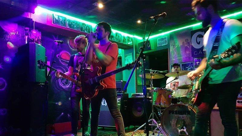 Foto de la banda en directo donde se ve a sus cuatro miembros sobre el escenario