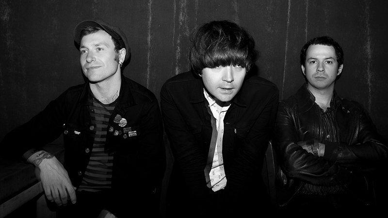 Foto en blanco y negro en la que se ve a los tres miembros de More Kicks sentados en un banco y posando con desgana