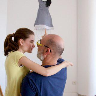 Foto de Pablo de Castro con su hija Jimena en brazos, tras ellos se ve la obra de Rebeca Menéndez