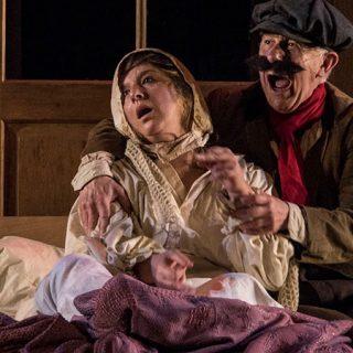 Imagen de la obra en la que se ve a dos de los personajes sentados, abrazándose y gritando