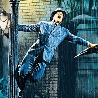 Clásico fotograma de la película en el que se ve a Gene Kelly agarrado a una farola con su mano derecha mientras sostiene un paraguas cerrado con la izquierda y canta boquiabierto mirando al cielo mientras llueve a mares