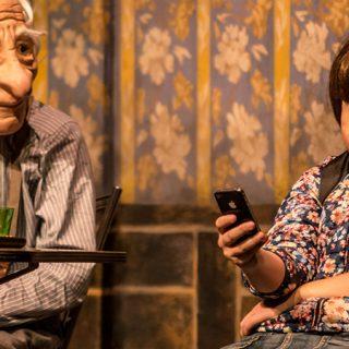Foto de una escena de Solitudes en la que se ve a dos personajes sentados uno junto a otro, el de la derecha mira el móvil y el de la izquierda le mira como esperando atención