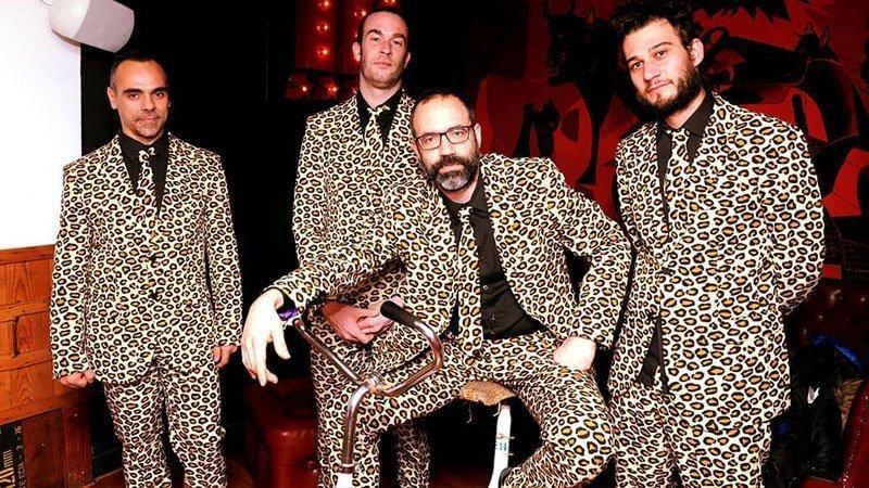 Foto de los 4 miembros de la banda vestidos con su caracterísitico traje con textuda de leopardo